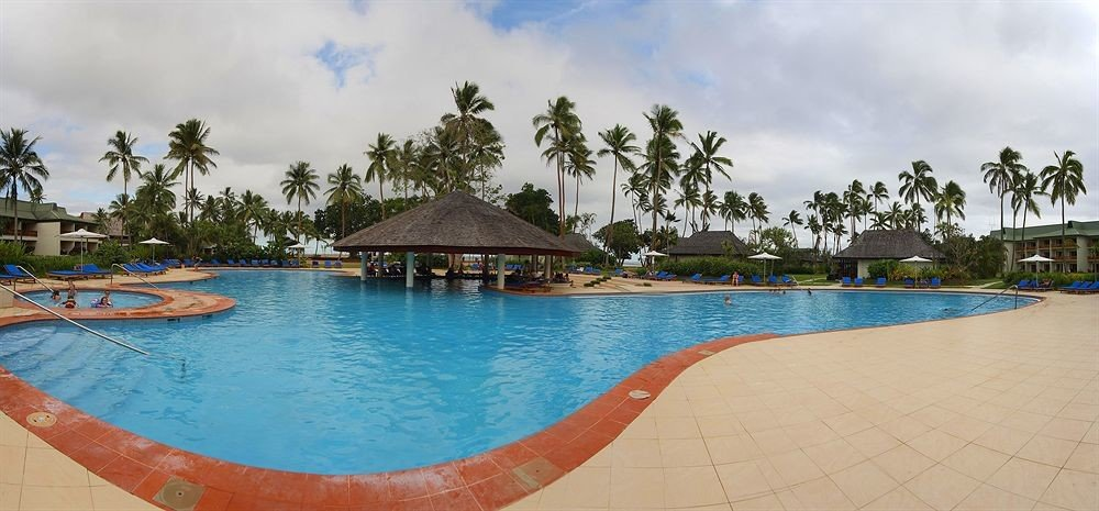 water sky Pool umbrella swimming pool leisure Resort swimming Sea Beach caribbean resort town Lagoon lined palm shore