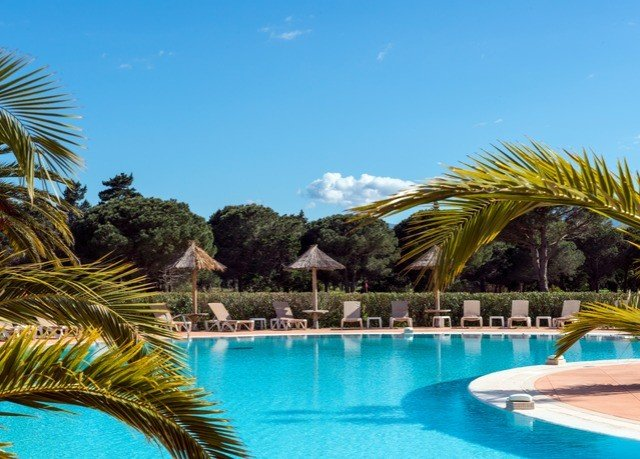 water Pool tree swimming pool Beach property Resort swimming caribbean leisure arecales Villa resort town Lagoon palm blue colorful