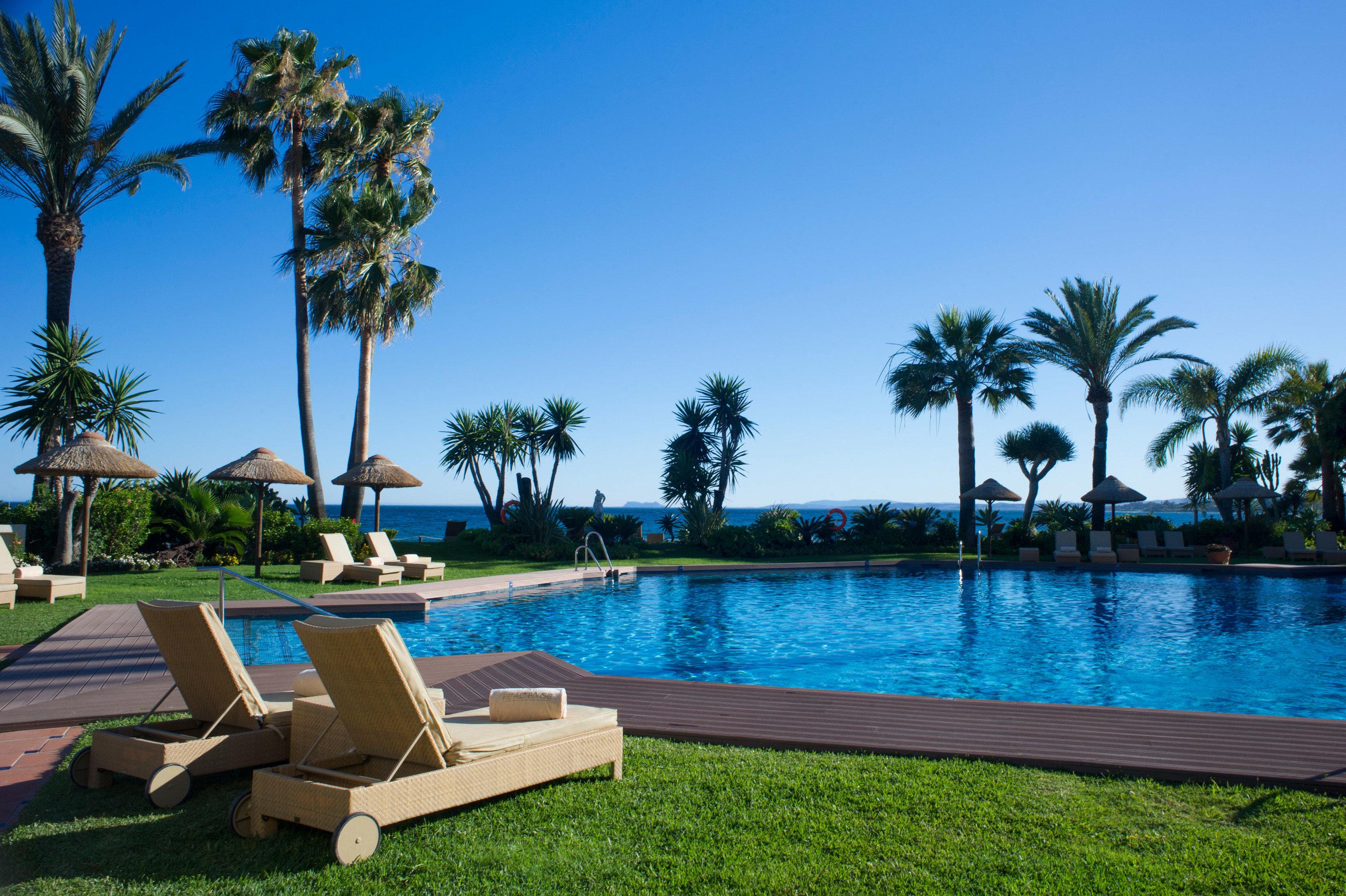 sky tree water grass umbrella chair palm swimming pool property leisure Resort lawn Villa caribbean arecales condominium backyard Beach mansion Pool overlooking