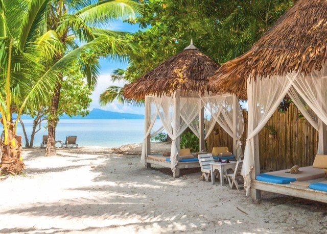 tree umbrella chair property Beach Resort caribbean palm lawn hut eco hotel sandy shade lined