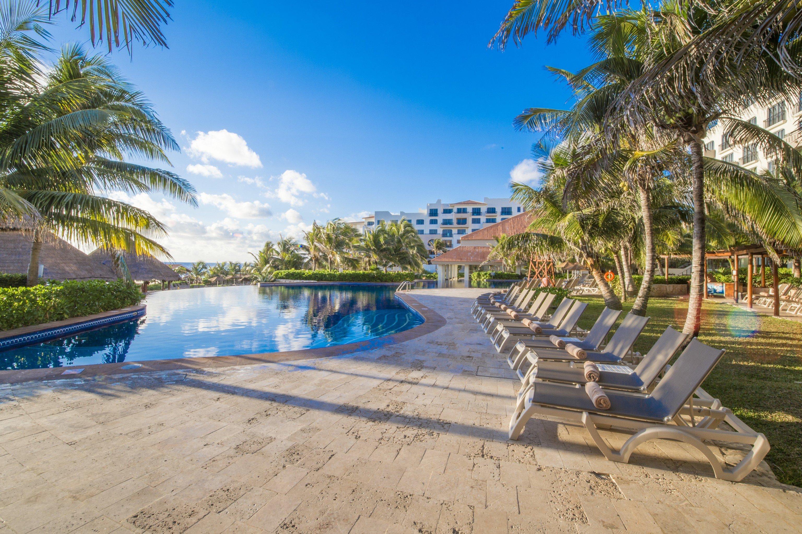 tree ground Resort water Beach property swimming pool leisure palm tree arecales resort town sky caribbean tropics Villa condominium hacienda shore plant lined sandy