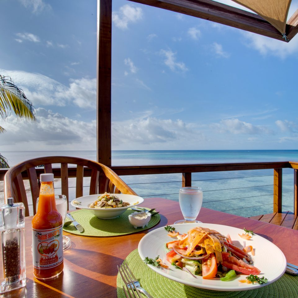 Beachfront Budget Dining Drink Eat Family Island Scenic views Tropical sky food leisure caribbean plate Resort restaurant swimming pool Villa home overlooking set dining table