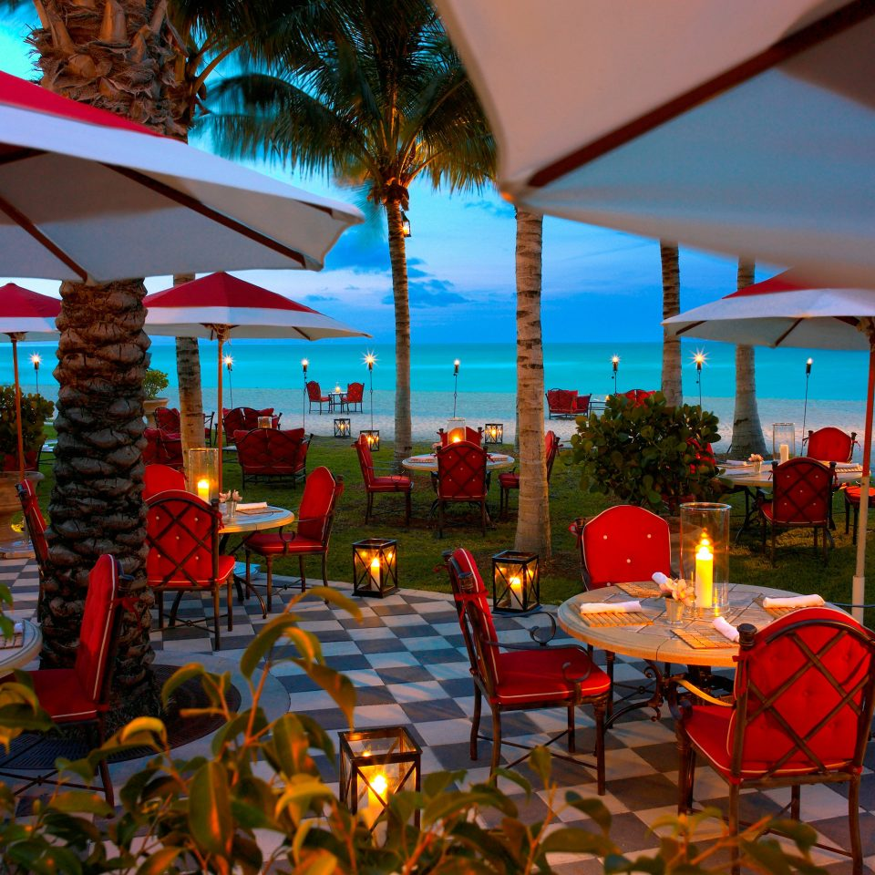 Beachfront Courtyard Dining Drink Eat Honeymoon Hotels Patio Romance Scenic views Terrace Waterfront umbrella chair Resort restaurant lawn colorful set