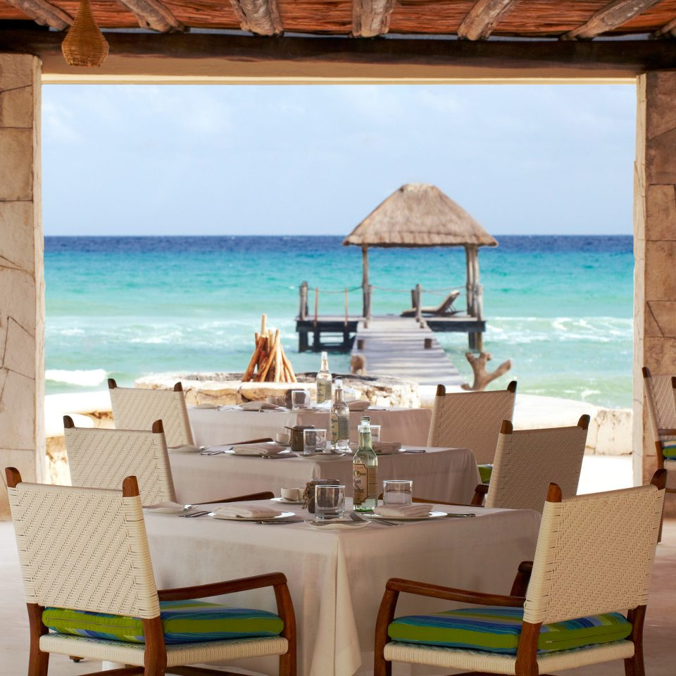 Beachfront Deck Dining Drink Eat Outdoors Patio Romantic Tropical chair property Resort Villa restaurant home cottage hacienda Island