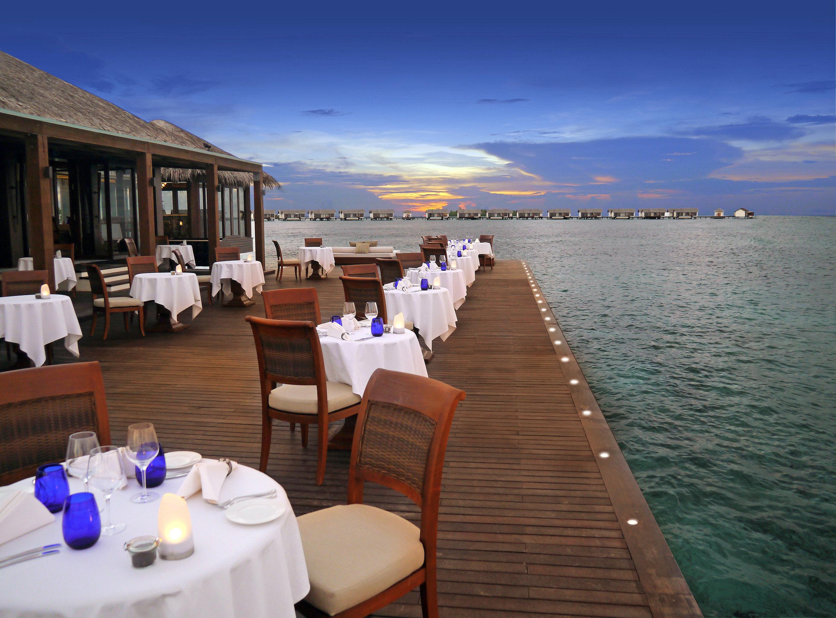 Beachfront Deck Drink Eat Elegant Luxury Ocean Romantic sky water wooden vehicle Resort passenger ship caribbean Sea restaurant overlooking Island