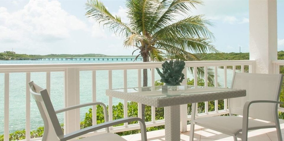 Beachfront Hip Lounge Luxury Tropical chair property porch condominium home Villa Resort cottage palm plant Deck dining table