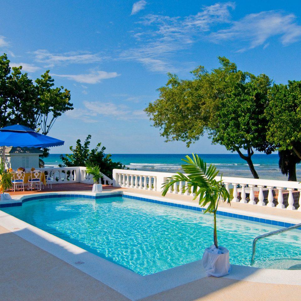 Beachfront Island Pool Waterfront tree swimming pool leisure property blue Resort Villa caribbean resort town backyard swimming Deck