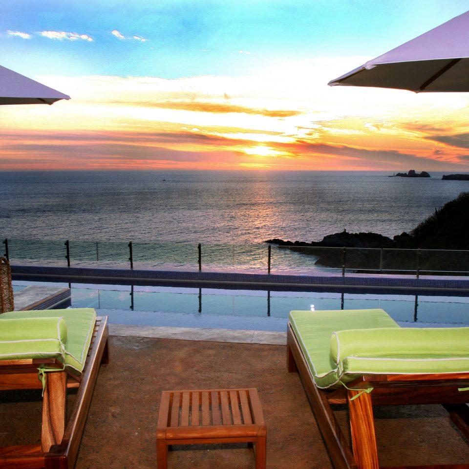 Beachfront Deck Lounge Sunset Tropical Waterfront sky chair water house caribbean Sea Resort Villa set overlooking shore