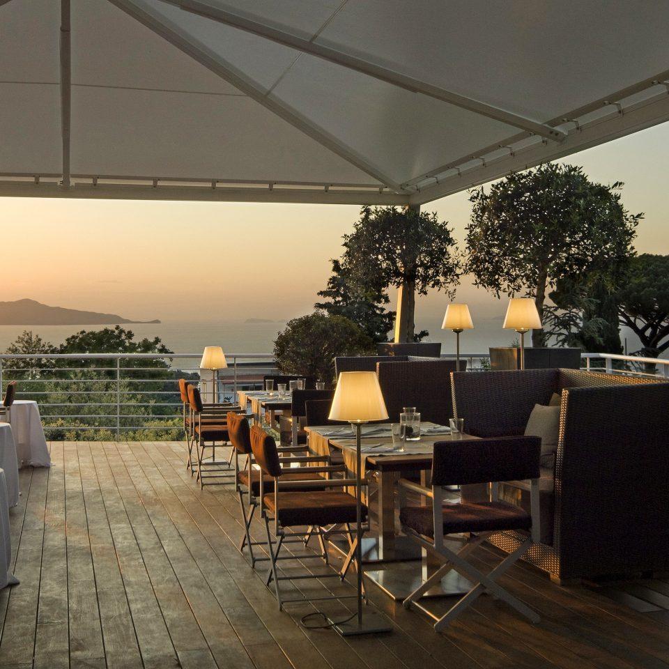 Beachfront Drink Eat Ocean Romantic Scenic views Sunset tree chair building restaurant outdoor structure Villa Resort