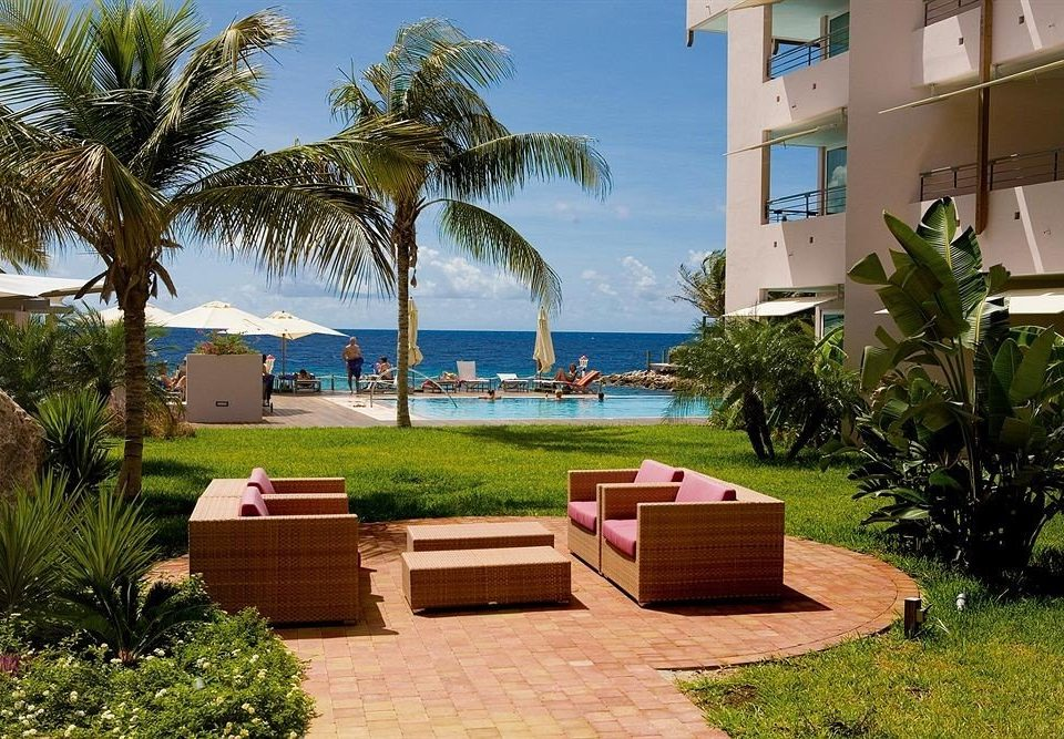 Beachfront Lounge Ocean tree grass palm property Resort sidewalk Villa swimming pool park home arecales plant condominium hacienda backyard caribbean walkway Garden shade