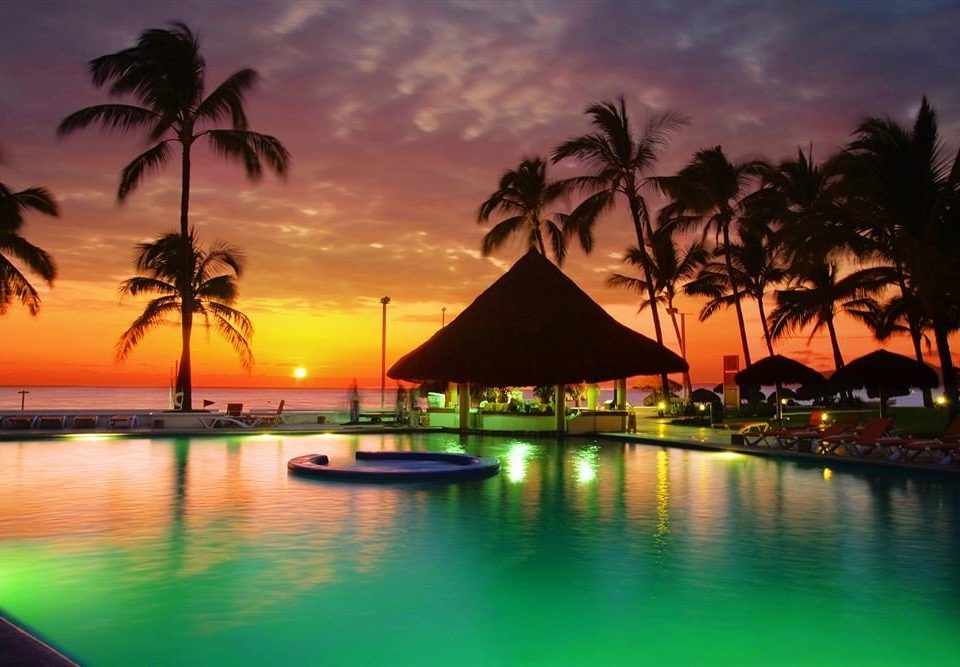 Beachfront Grounds Ocean Patio Pool Romance Sunset Tropical water Resort arecales dusk evening tree caribbean palm Lagoon tropics plant shore