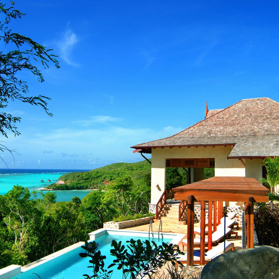 Beachfront Island Lounge Patio Pool Resort Tropical tree sky property house Villa swimming pool home cottage hut Village caribbean