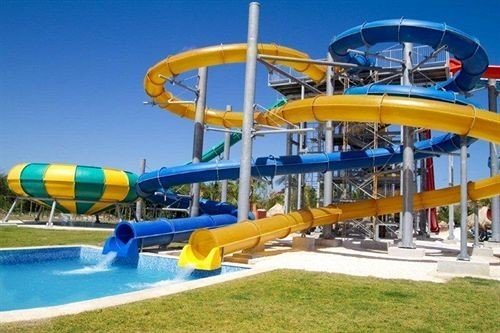 Beachfront Lounge Pool Tropical grass sky amusement park Water park park yellow leisure recreation outdoor object outdoor recreation amusement ride nonbuilding structure Playground playground slide blue colorful