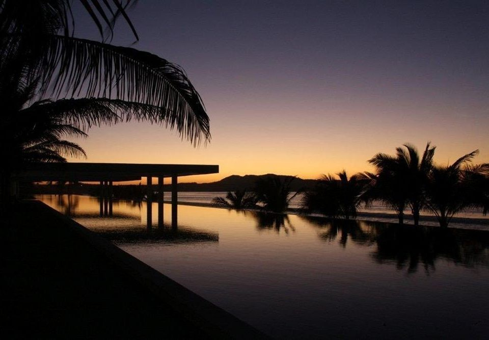 Beachfront Lounge Pool Ranch Tropical water sky tree palm Sunset night horizon dawn dusk evening sunrise morning Sun plant darkness arecales sunlight Sea setting shore