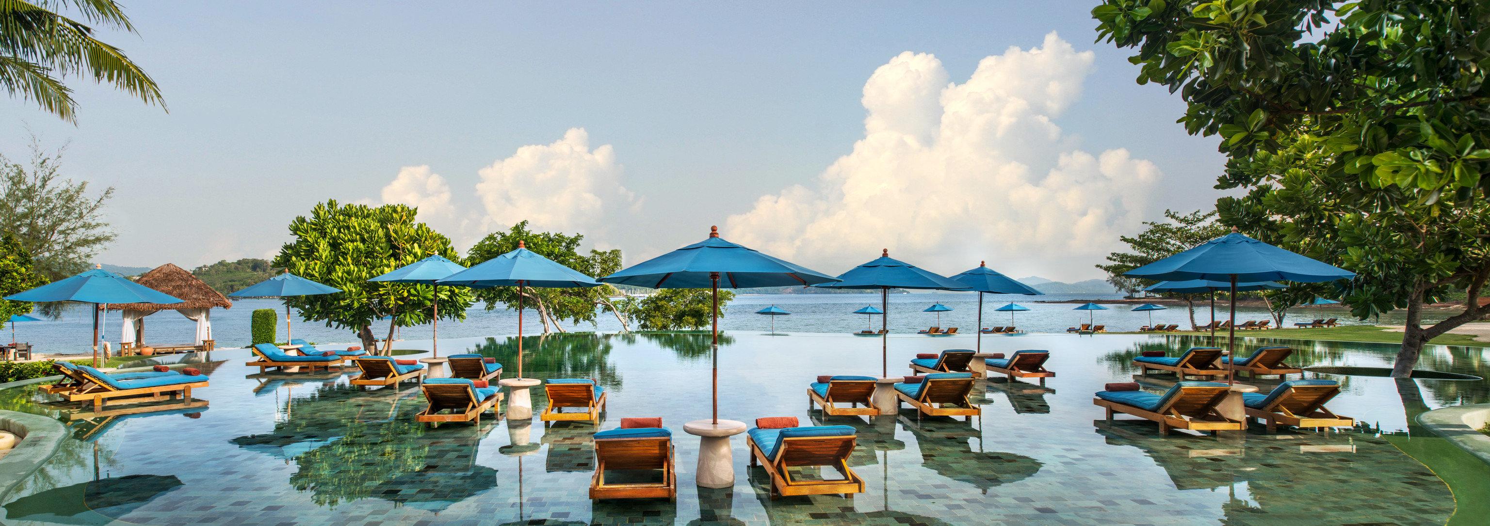 Beach Hotels Phuket Thailand Resort leisure swimming pool tourism resort town vacation tropics caribbean palm tree Lagoon tree arecales water real estate recreation estate sky bay
