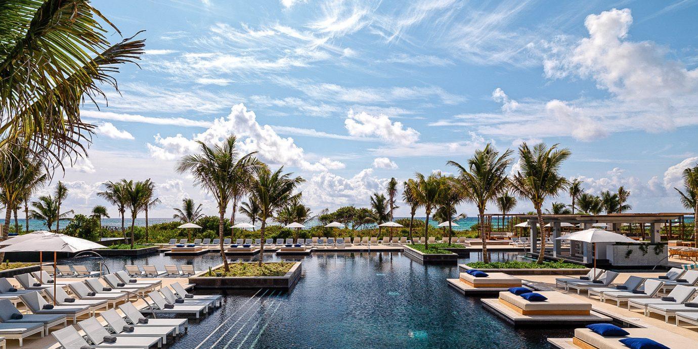 Boutique Hotels Hotels Luxury Travel sky water tree Boat Resort waterway swimming pool palm tree arecales leisure marina dock tropics docked resort town caribbean condominium Sea cloud plant lined