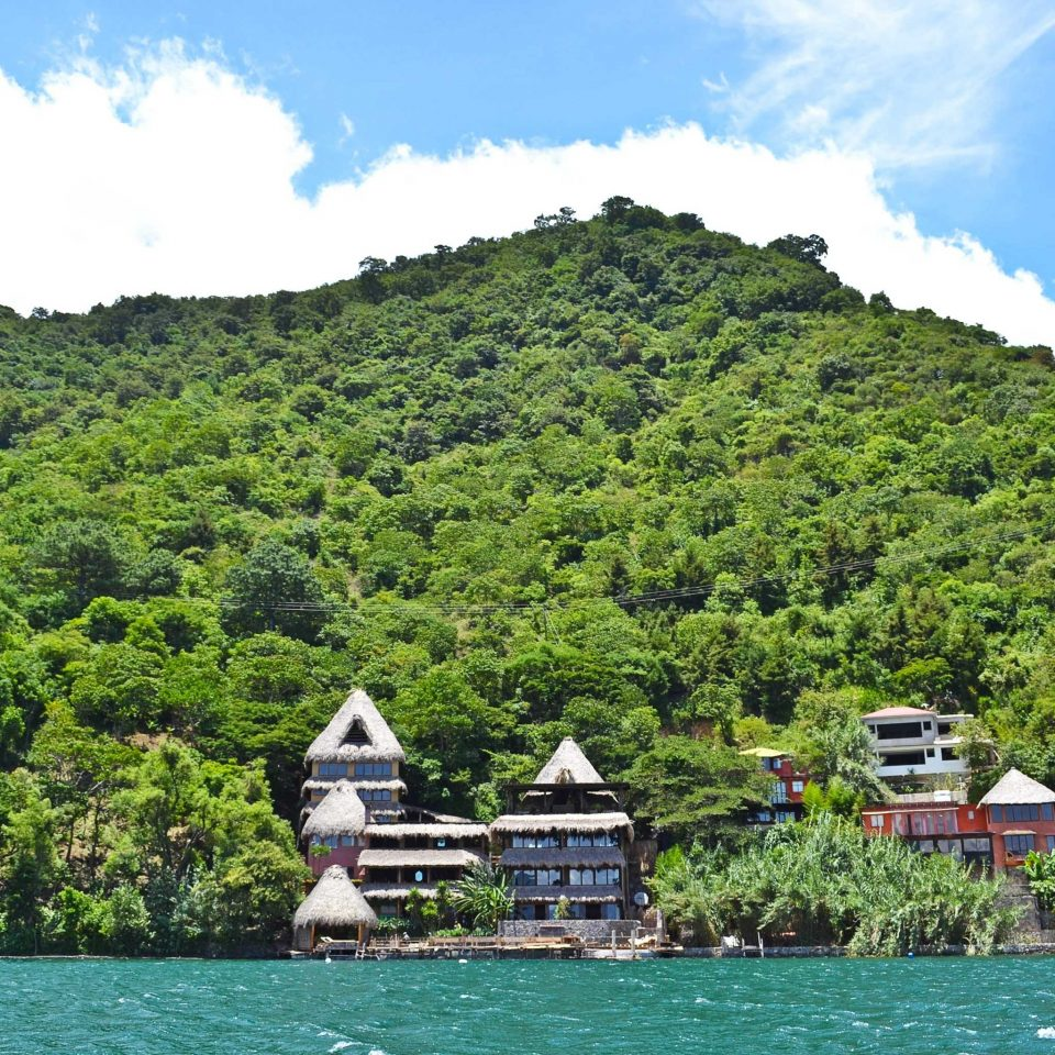 Buildings Exterior Forest Island Jungle Ocean Sea sky water mountain Boat Lake River mountain range Nature fjord surrounded highland