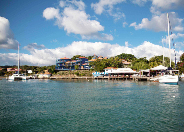 sky water scene Boat Sea Harbor Town marina dock vehicle caribbean Coast docked clouds Lagoon Island day surrounded