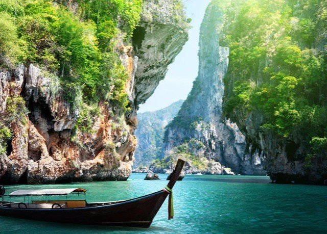 water tree mountain Boat watercraft transport sea cave Waterfall water feature Jungle formation terrain cliff