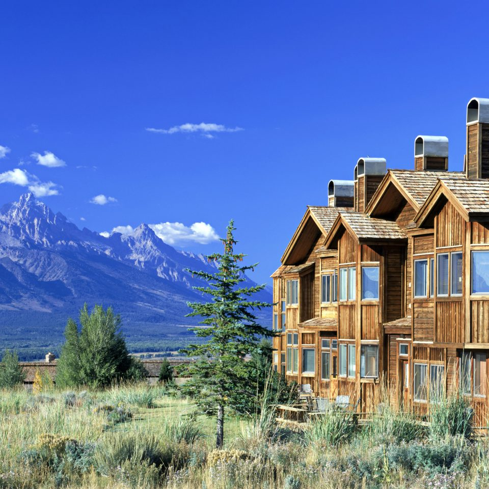 Budget Country Family Lodge Mountains Outdoor Activities Outdoors sky grass mountainous landforms mountain tree house building residential area mountain range home landscape rural area log cabin tall