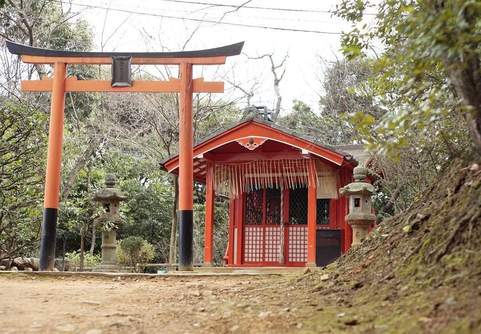 tree ground building shinto shrine shack shrine outdoor structure cottage torii hut house dirt hillside