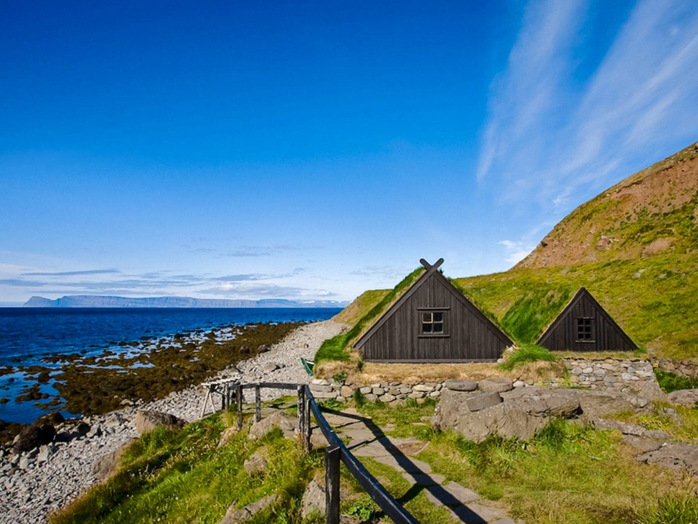 Iceland Travel Tips grass sky outdoor mountainous landforms mountain Sea landform Coast geographical feature Ocean vacation cloud horizon hill house shore Nature landscape cliff mountain range rock rural area cape terrain bay hillside stone lush highland