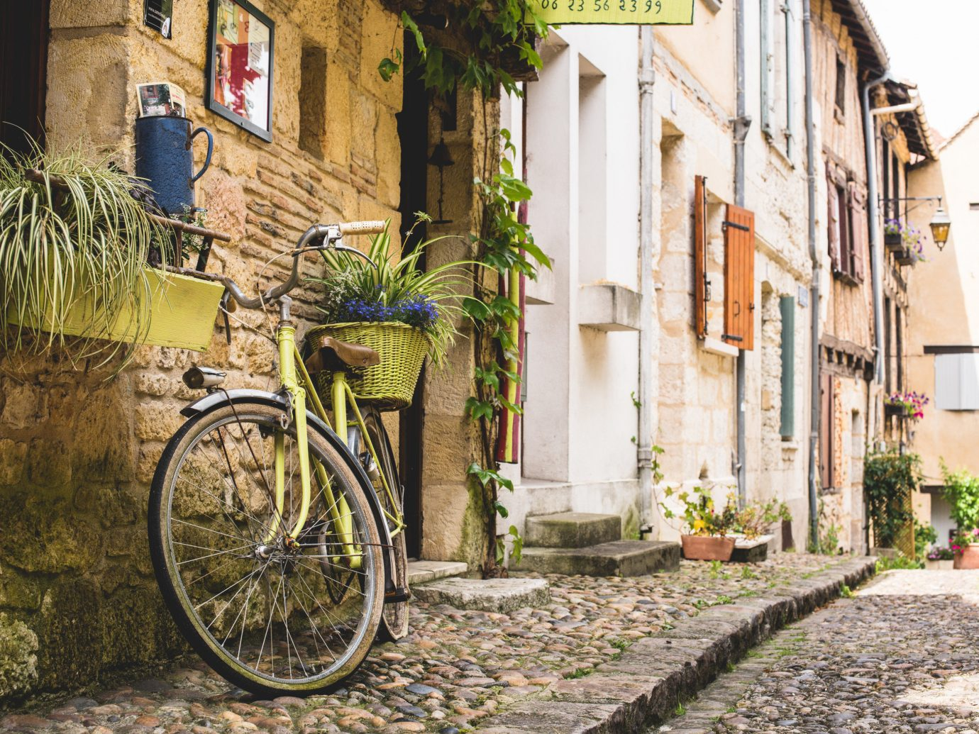 Health + Wellness Meditation Retreats Trip Ideas Yoga Retreats outdoor bicycle building ground way road parked Town lane neighbourhood street residential area alley scene human settlement sidewalk Village infrastructure suburb cycling vehicle mountain bike stone curb
