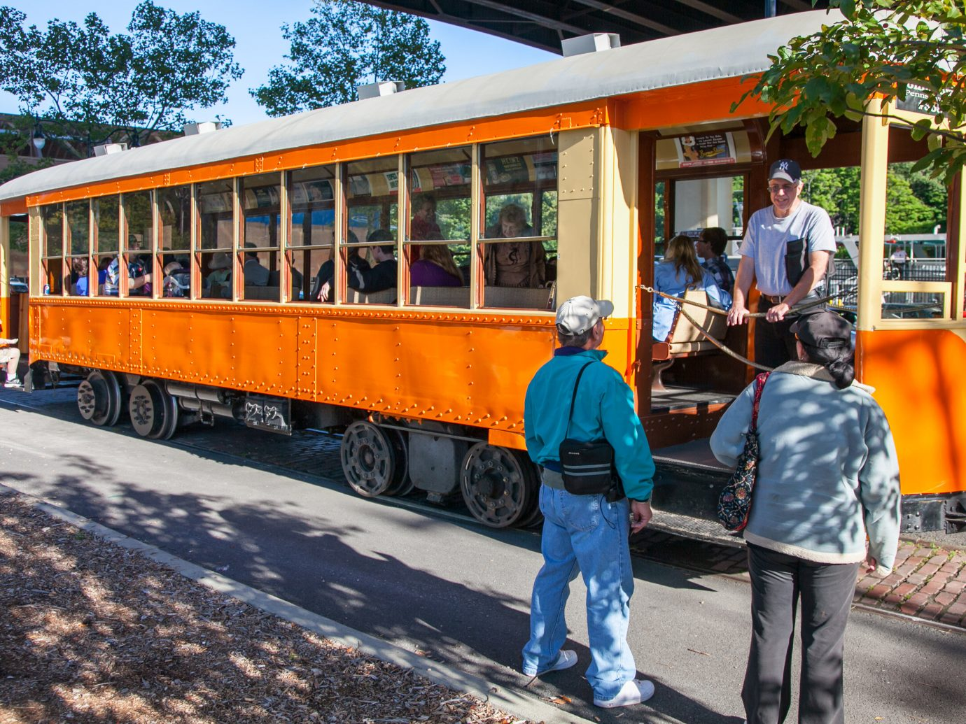 Food + Drink outdoor tree ground person vehicle transport land vehicle rolling stock cable car tourism public transport people tram passenger train bus