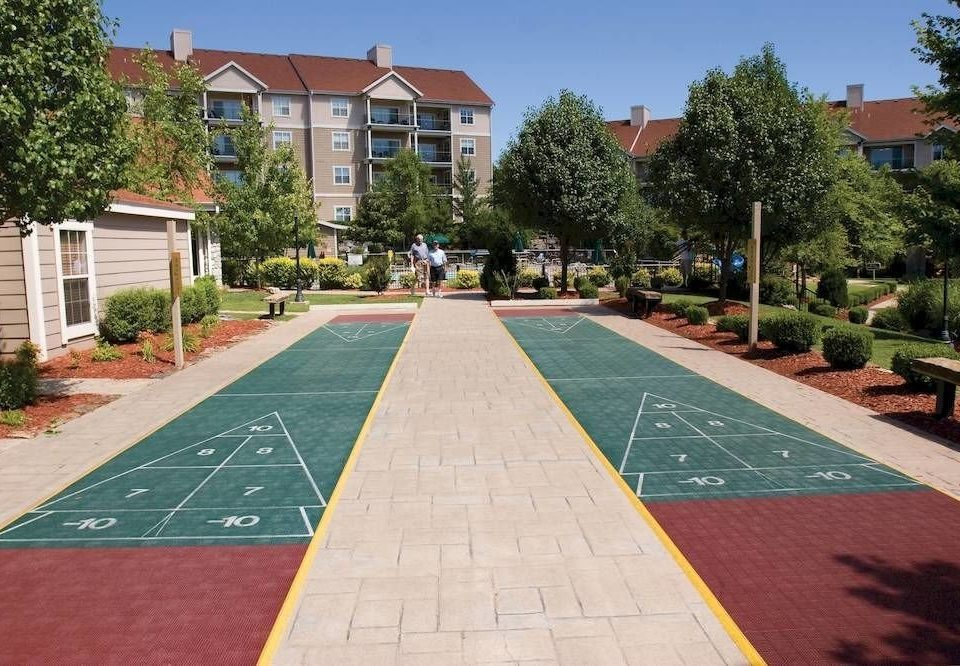 tree ground plaza walkway sidewalk City public space Sport street town square brick neighbourhood residential area athletic game lawn Playground swimming pool home Garden Courtyard Resort backyard outdoor structure yard curb
