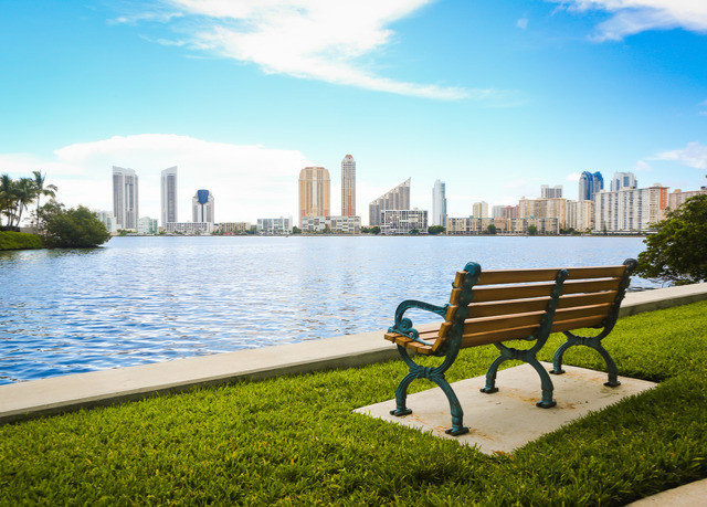 bench sky water grass park leisure overlooking City Lake skyline facing swimming pool shore day