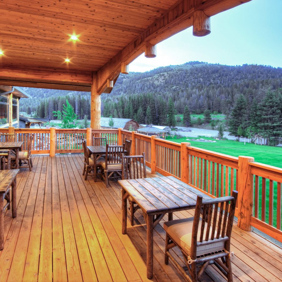 Country Deck Glamping Hotels Lodge Montana Outdoors + Adventure Patio Ranch Rustic Scenic views Trip Ideas wooden chair building property Resort cottage outdoor structure Villa porch log cabin eco hotel