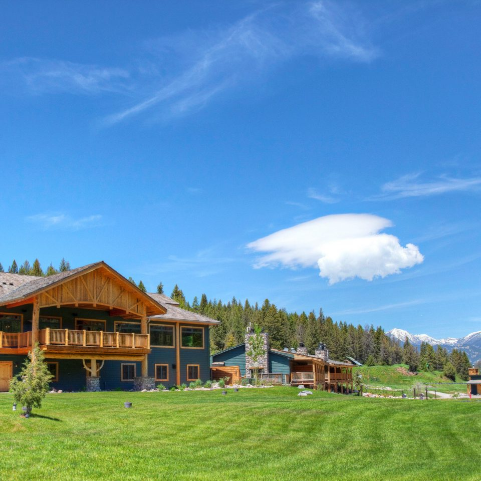 Country Exterior Glamping Grounds Hotels Lodge Montana Nature Outdoors Outdoors + Adventure Ranch Rustic Trip Ideas grass sky mountainous landforms house field mountain range mountain green rural area old landscape Resort valley meadow Village Farm plateau grassy lush hillside