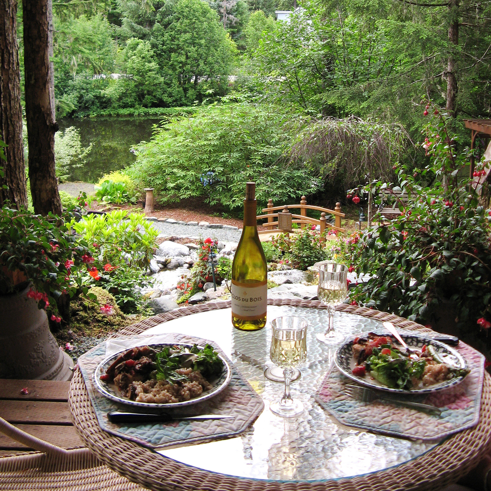 Dining Drink Eat Lodge Outdoors tree plate Garden flora botany backyard flower yard plant water feature Courtyard set Forest surrounded