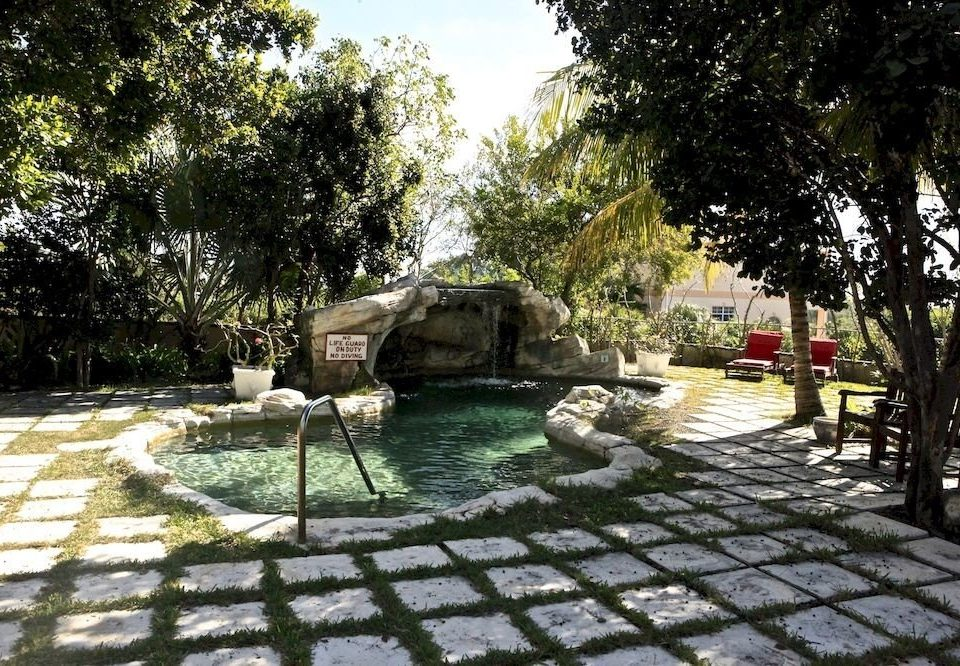 tree property backyard park yard home cottage Villa Courtyard way swimming pool Garden pond outdoor structure Patio landscaping plant surrounded stone paving day