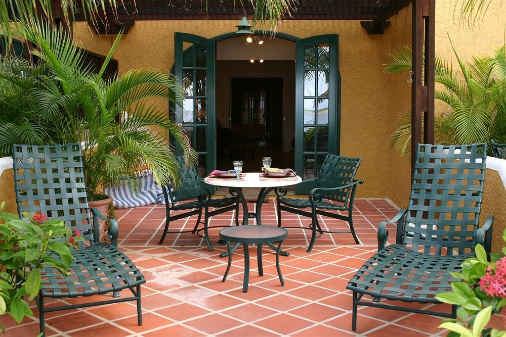 property green chair backyard Resort home Courtyard Villa outdoor structure hacienda restaurant porch condominium cottage plant Patio arranged dining table