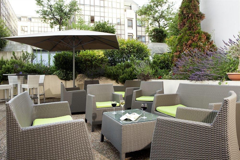 tree chair green property outdoor structure backyard Patio Courtyard wicker yard Villa condominium porch set