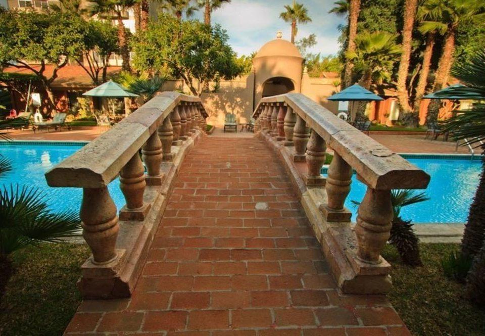 tree property Resort walkway swimming pool Villa hacienda sidewalk mansion backyard home Courtyard cottage stone