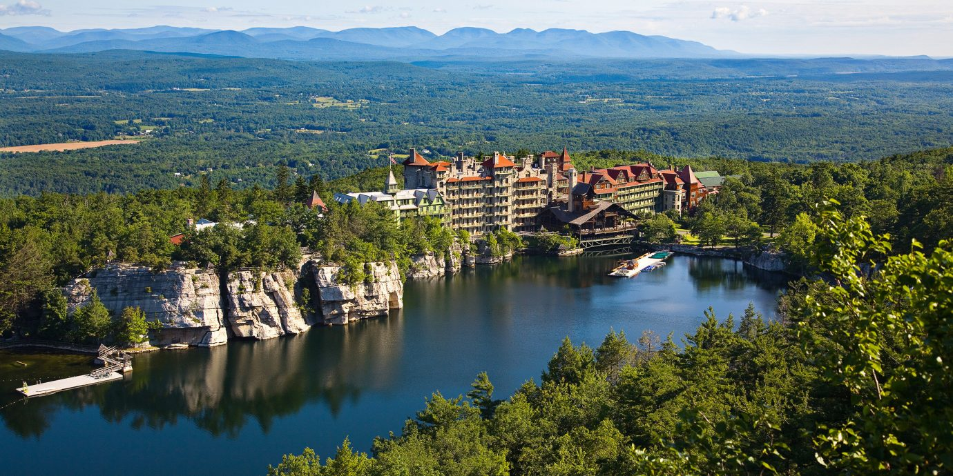 Classic Hotels Lake Lakes + Rivers Luxury Mountains New York Outdoor Activities Resort Romance Romantic Hotels Trip Ideas mountain tree outdoor water sky Nature mountainous landforms reflection body of water aerial photography River hill mountain range landscape tourism reservoir overlooking autumn Sea hillside surrounded