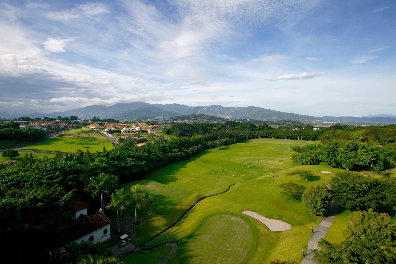 Cultural Natural wonders Scenic views sky grass structure Nature hill aerial photography sport venue green golf course field plain mountain rural area landscape golf club grassy lush meadow plateau valley hillside overlooking highland