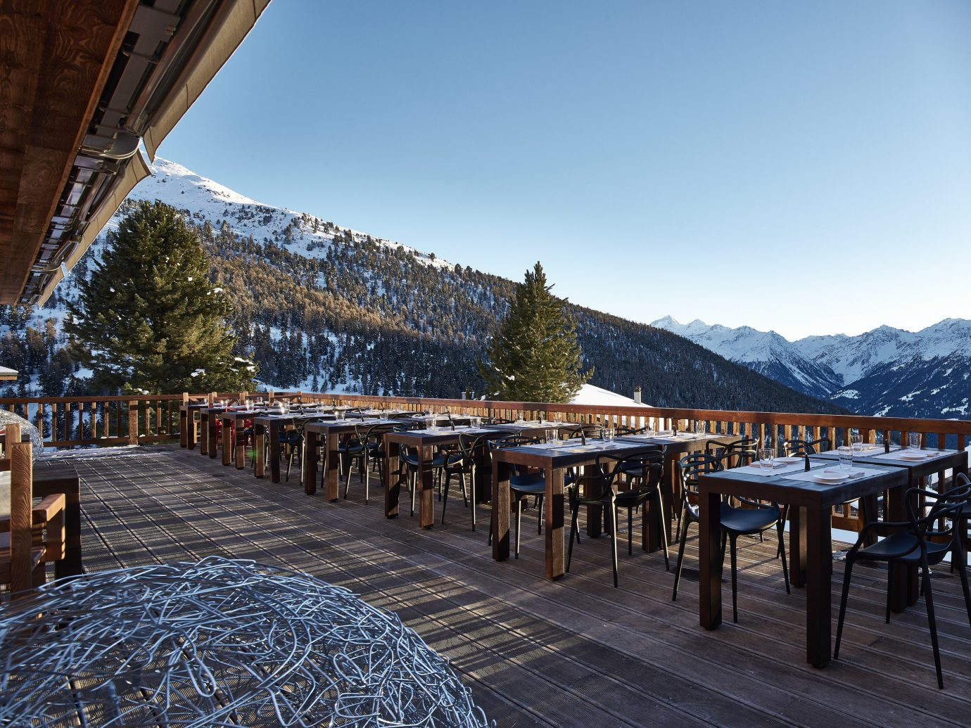 Boutique Hotels Hotels Outdoors + Adventure sky outdoor ground Winter snow chair mountainous landforms mountain Town mountain range wooden tree water real estate reflection landscape City evening cloud plant alps house bridge roof