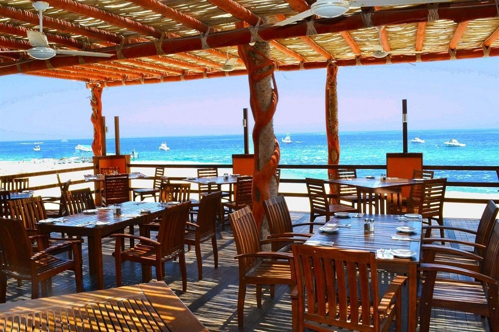 Dining Drink Eat Ocean Rustic Scenic views chair sky water umbrella wooden property Resort restaurant caribbean lawn Villa set lined Deck