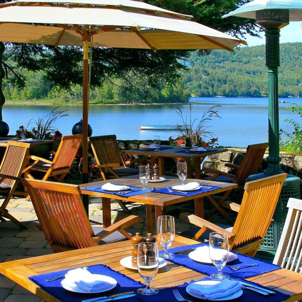 Dining Drink Eat Luxury Patio Resort Waterfront tree umbrella chair leisure restaurant lawn set cottage Deck empty day