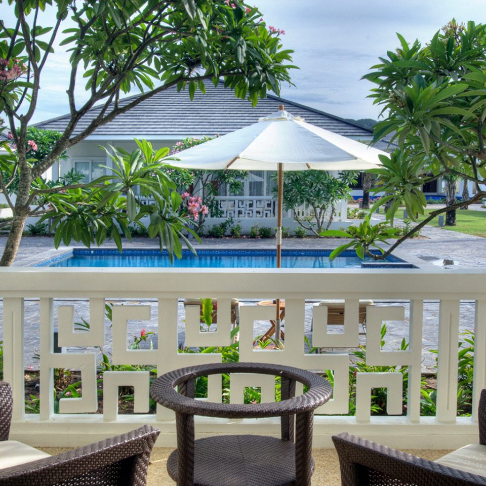 Eco Elegant Grounds Jungle Nature Patio Pool Scenic views Sea Tropical Waterfront tree chair property Resort Villa home condominium white caribbean mansion porch outdoor structure eco hotel backyard cottage Deck