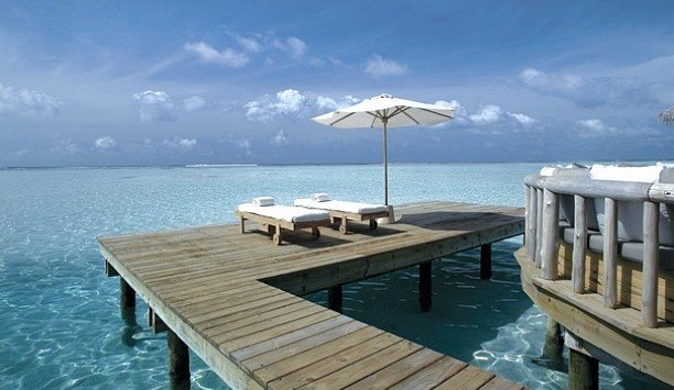 sky water umbrella Sea wooden Resort coastal and oceanic landforms sunlounger Ocean Nature outdoor furniture Deck swimming pool shore leisure dock Lagoon condominium caribbean overlooking day