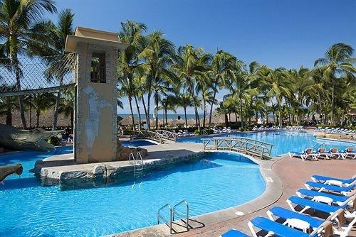tree Pool swimming pool Resort property chair leisure caribbean marina Villa resort town Lagoon blue condominium lawn swimming Water park palm Deck shore sandy