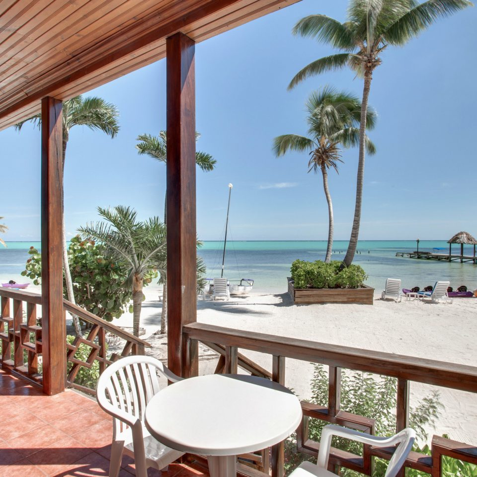 sky chair tree ground umbrella property building Resort porch leisure Deck Villa caribbean Ocean home Pool cottage condominium eco hotel overlooking shade dining table
