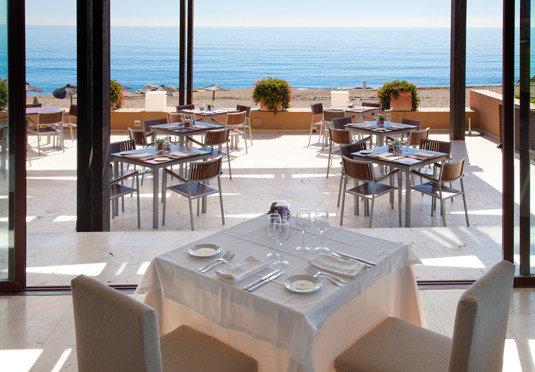 chair water Ocean property restaurant Resort condominium Villa overlooking set Deck dining table