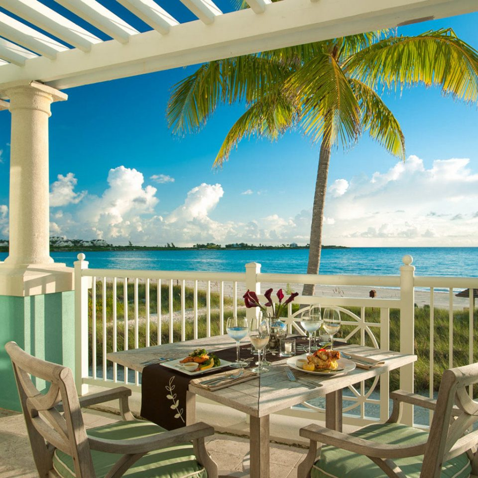 chair property caribbean leisure Resort porch swimming pool Villa Pool condominium Deck home lawn eco hotel cottage mansion overlooking shore dining table