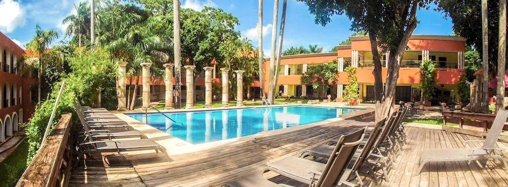 tree sky ground building property leisure Resort swimming pool condominium wooden Villa resort town Pool Deck hacienda eco hotel lined palm empty