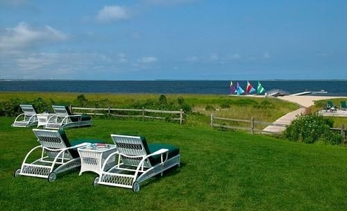 grass sky property ecosystem lawn Villa cottage Deck chair seat overlooking shore lush